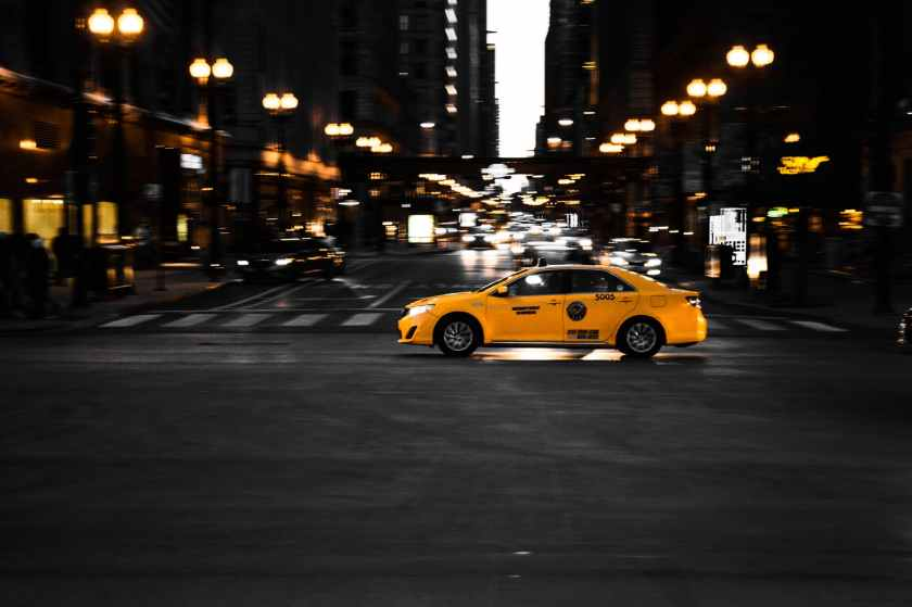 photography of yellow taxi on road
